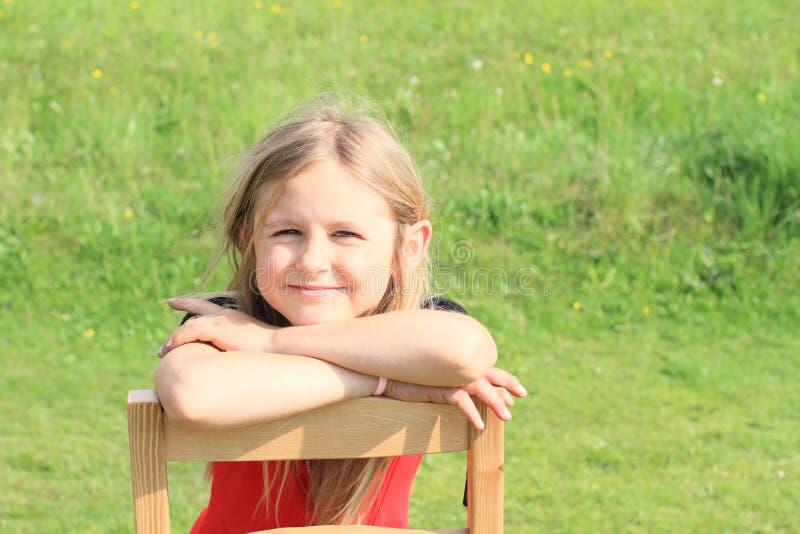 Mädchen, das auf Stuhl sich lehnt lizenzfreie stockbilder