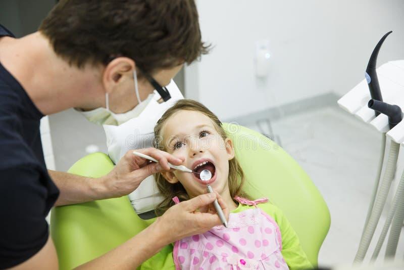 Mädchen, das auf zahnmedizinischem Stuhl auf ihrer regelmäßigen zahnmedizinischen Überprüfung sitzt stockfoto