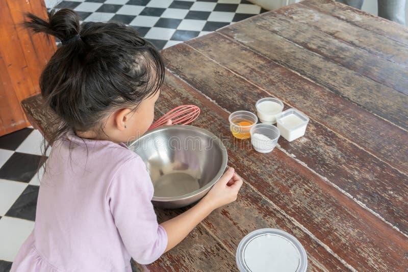 Mädchen, das Aufmerksamkeit auf Bestandteilen für selbst gemachte Eiscreme zahlt stockfotos