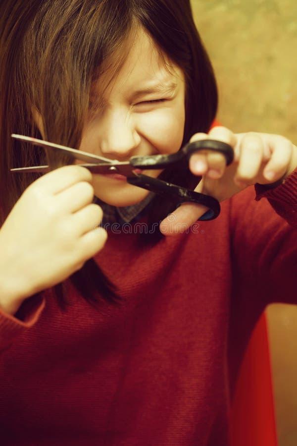 Mädchen, das Augen von der Furcht beim Schnitt des Haares verengt lizenzfreies stockfoto
