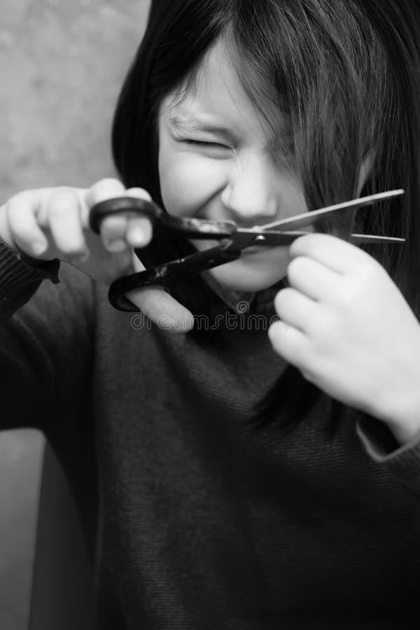 Mädchen, das Augen von der Furcht beim Schnitt des Haares verengt lizenzfreie stockfotos