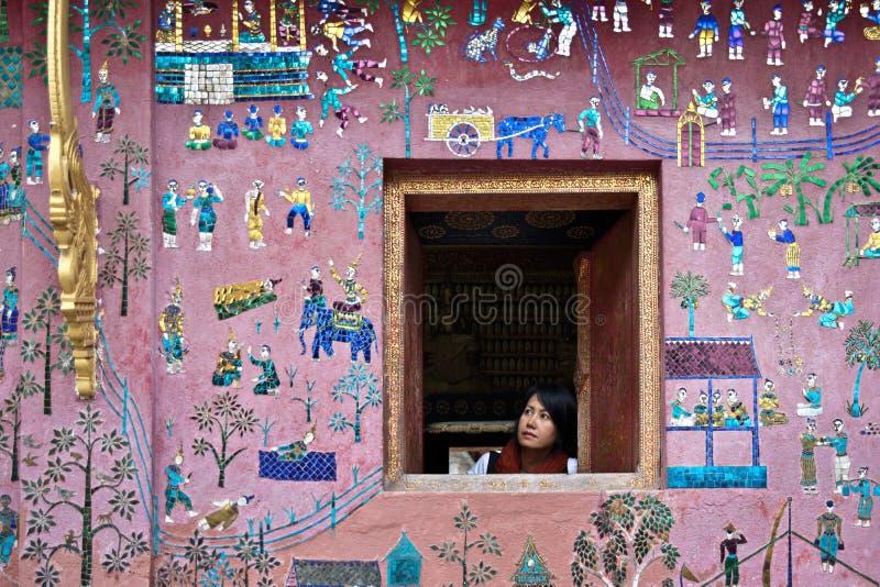 Mädchen, das aus dem Fenster mit schöner Wand heraus schaut stockbild