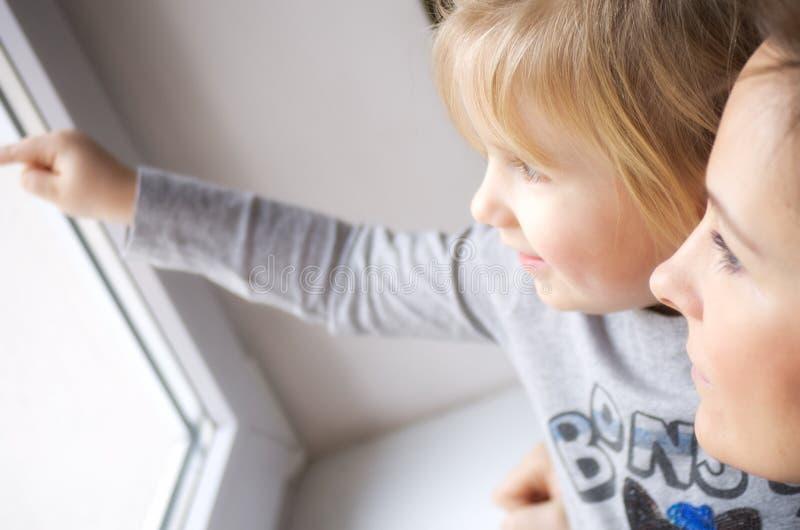 Mädchen, das aus Fenster heraus schaut stockfotos