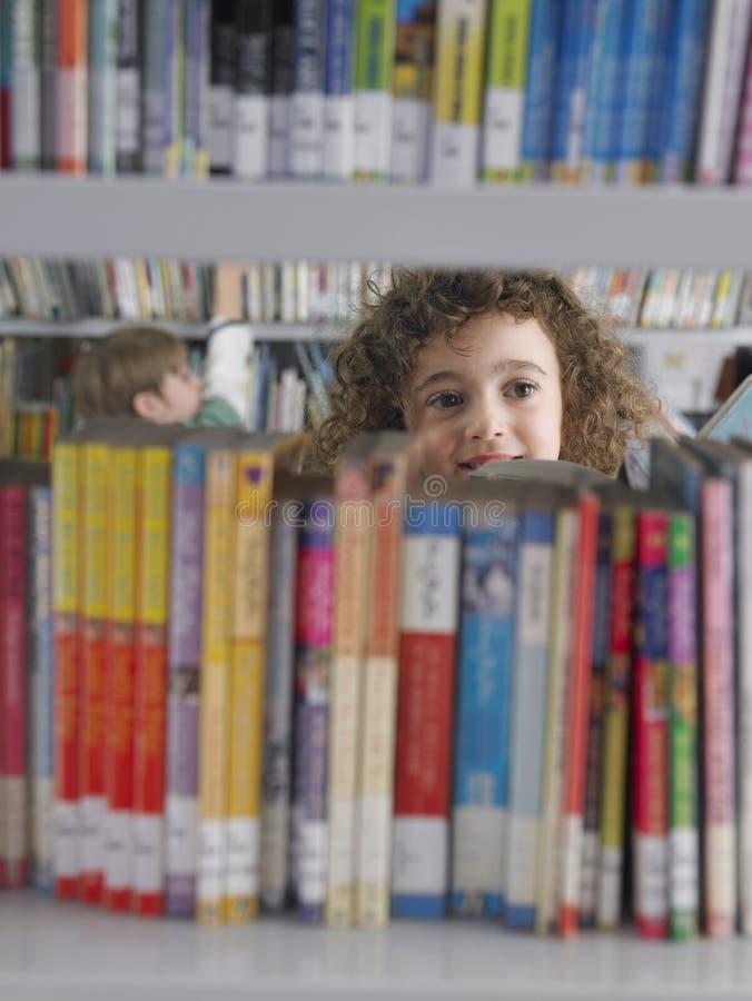 Mädchen, das Bücher vom Bibliotheks-Bücherregal vorwählt lizenzfreies stockfoto