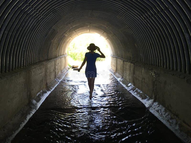 Mädchen, das barfuß durch das Wasser in einem dunklen Tunnel zum Licht geht lizenzfreies stockfoto