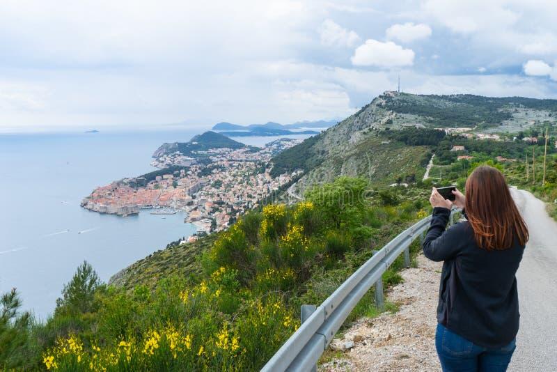 Mädchen, das Bilder von Dubrovnik auf dem Hügel mit einem intelligenten Telefon in einer kleinen Straße zur alten Stadt in Kroati stockfotografie