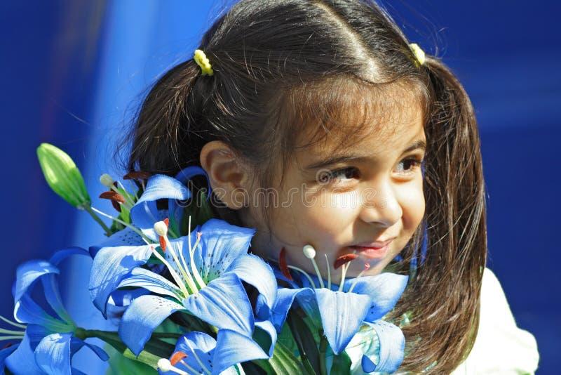 Mädchen, das blaue Blumen anhält stockfotografie