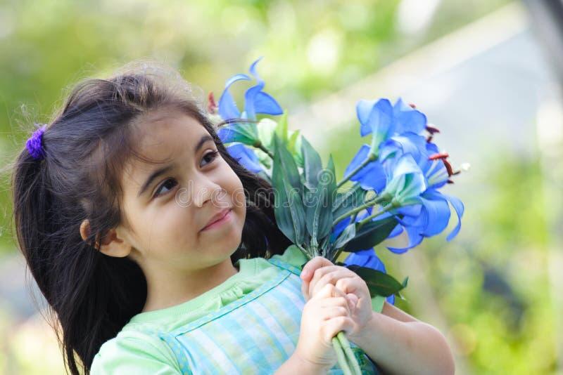 Mädchen, das blaue Blumen anhält lizenzfreie stockbilder