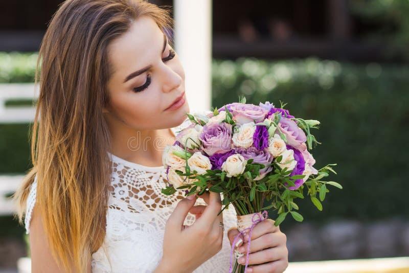 Mädchen, das Blumen in den Händen, junge schöne Braut im weißen Kleid hält Hochzeitsblumenstrauß, Blumenstrauß der Braut vom rosa stockfoto