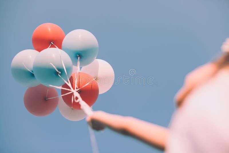 Mädchen, das bunte Ballone oben in der luft- niedrigen Winkelsicht hält stockfotografie