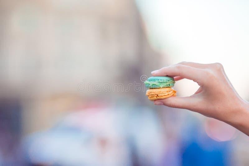 Mädchen, das bunte französische macarons in der lebhaften Straße des Handhintergrundes hält lizenzfreies stockbild