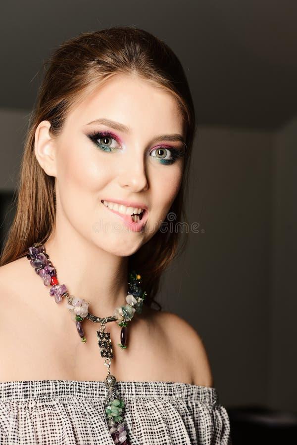 Mädchen, das buntes Make-up tragen und Halskette, die ihre Lippe beißt lizenzfreies stockfoto