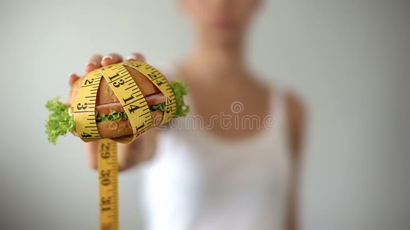 Mädchen, das Burger gebunden mit messendem Band, ungesunde Fertigkost, ungesunder Lebensstil hält lizenzfreie stockfotografie