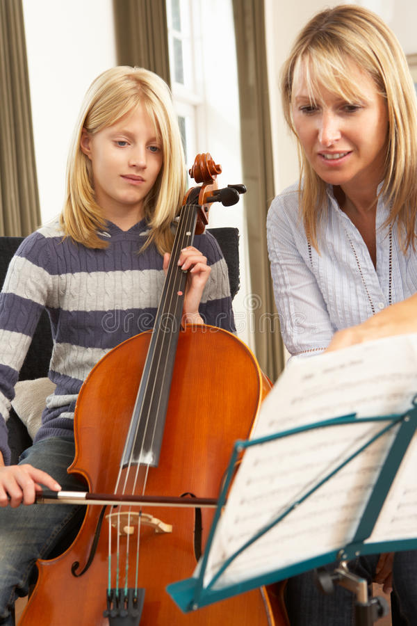 Mädchen, das Cello in der Musiklektion spielt lizenzfreie stockfotografie