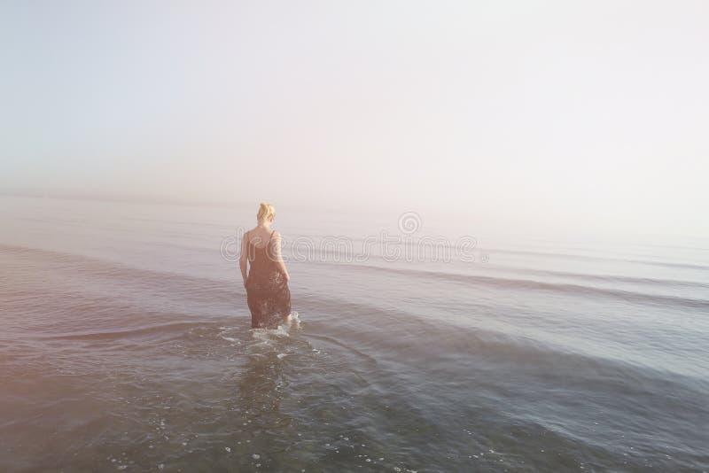 Mädchen, das in das Wasser geht lizenzfreies stockbild