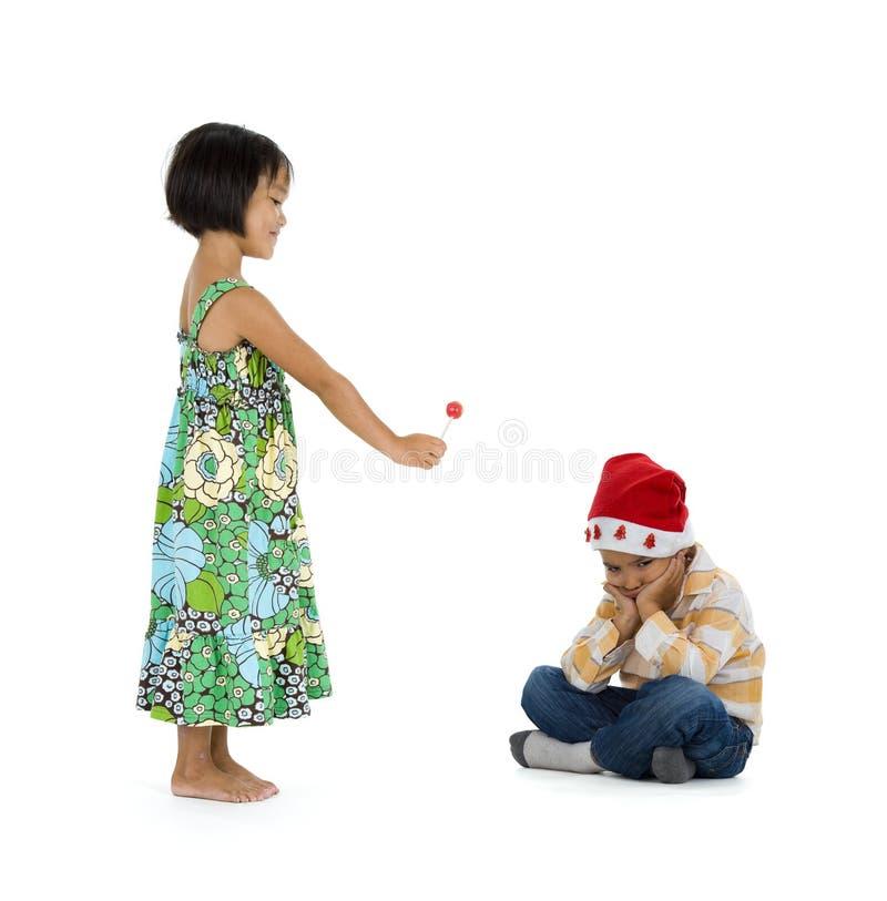 Mädchen, das dem Jungen Weihnachtsgeschenk gibt stockbild