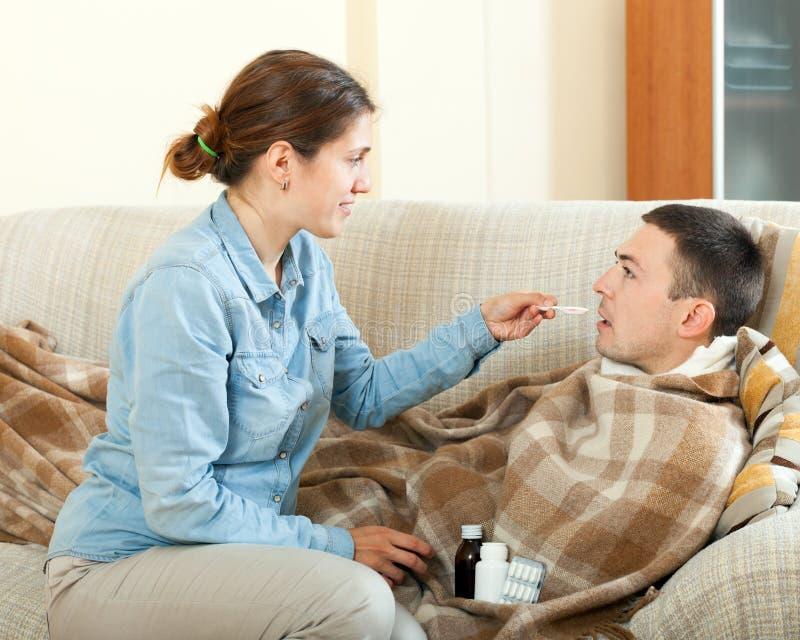 Mädchen, das dem unwohlen Ehemann Medikament gibt lizenzfreies stockfoto