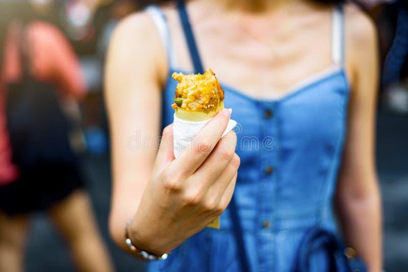 Mädchen, das den Hühnerflügel geschnüffelt mit Reis isst lizenzfreies stockfoto