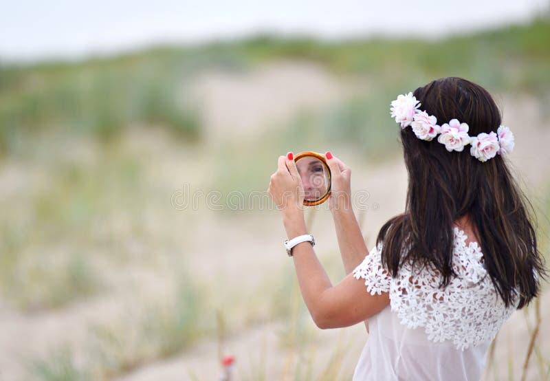 Mädchen, das den kleinen runden Spiegel betrachtet stockfoto