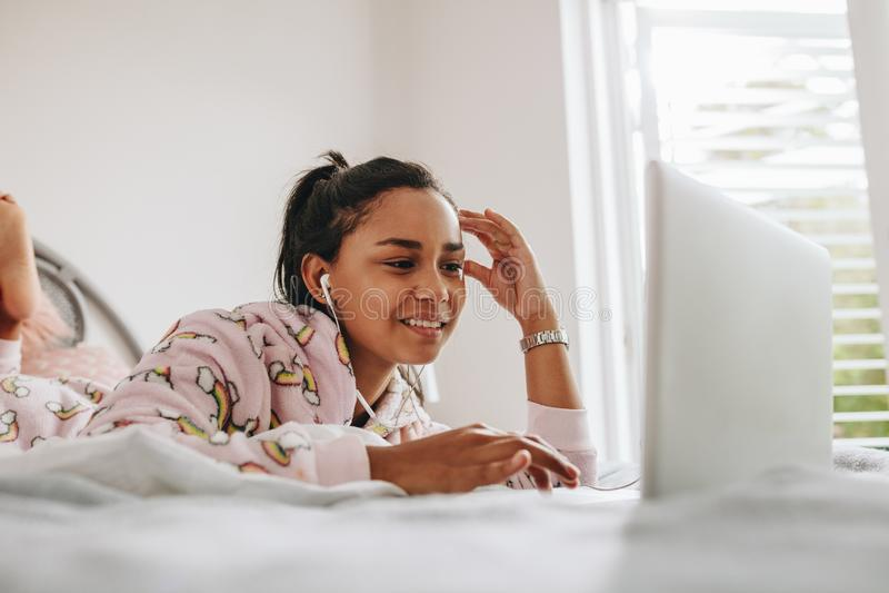 Mädchen, das den Laptop liegt auf Bett verwendet stockfotografie