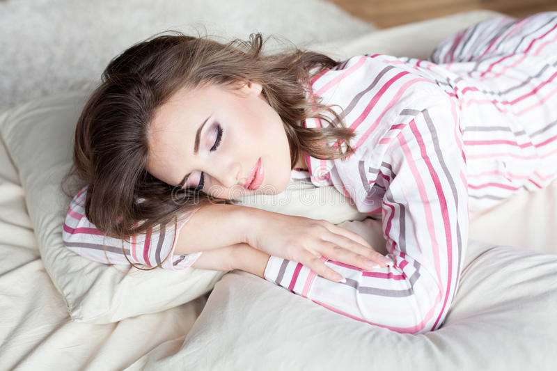 Mädchen, das in den Pyjamas mit Make-up schläft stockbilder