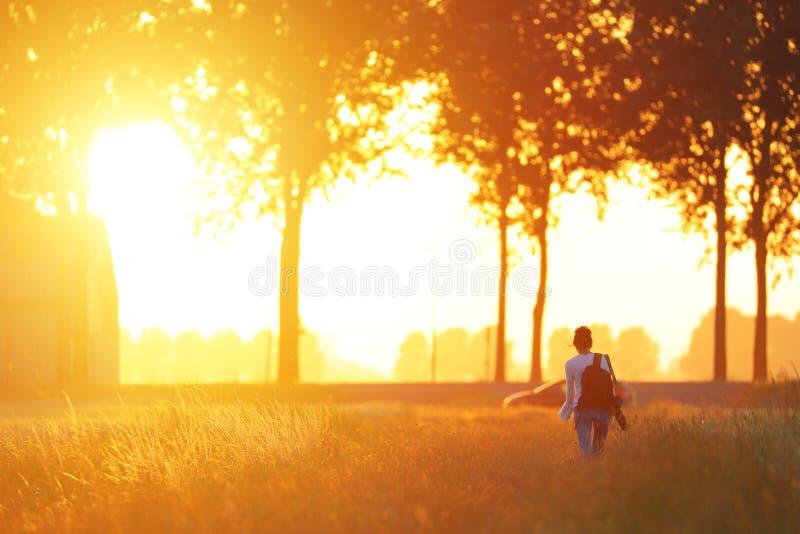 Mädchen, das in den Sonnenuntergang geht lizenzfreie stockfotografie
