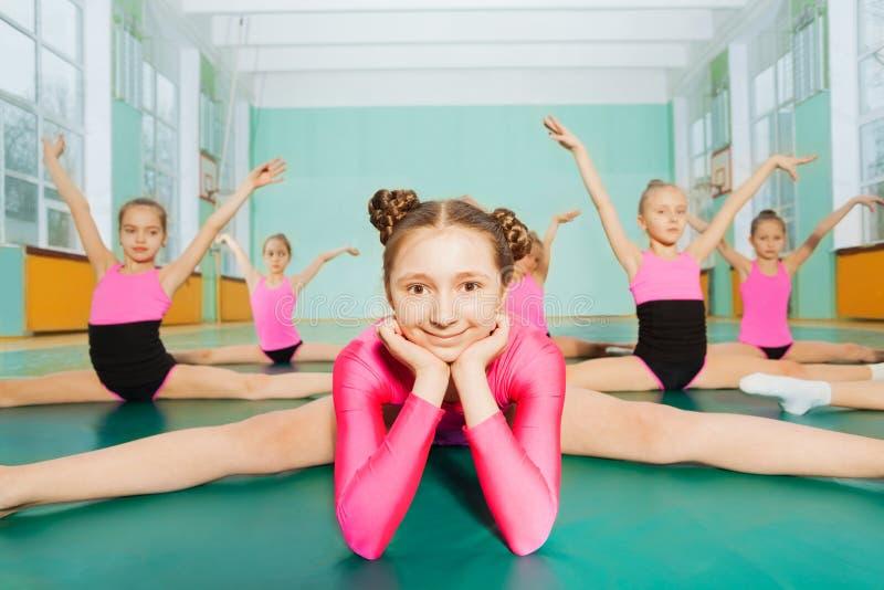 Mädchen, das in den Spalten während der Gymnastikklasse sitzt stockbild