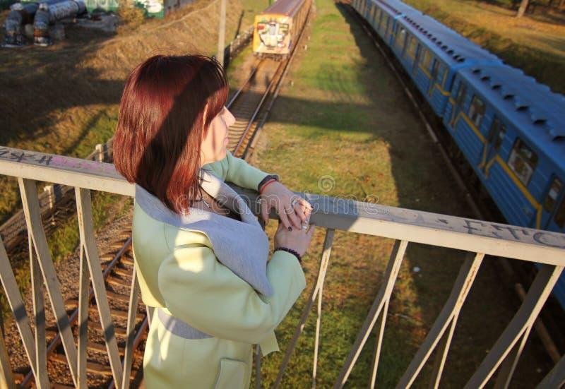 Mädchen, das den Zug betrachtet, der eine Brücke kreuzt Junges schönes Mädchen, das nahe Eisenbahnlinien geht, wohin die Züge lau lizenzfreie stockbilder