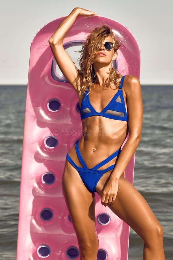 Mädchen, das in der Hand auf aufblasbarem Kreis des Rosas des Strandes ein Sonnenbad nimmt stockbild