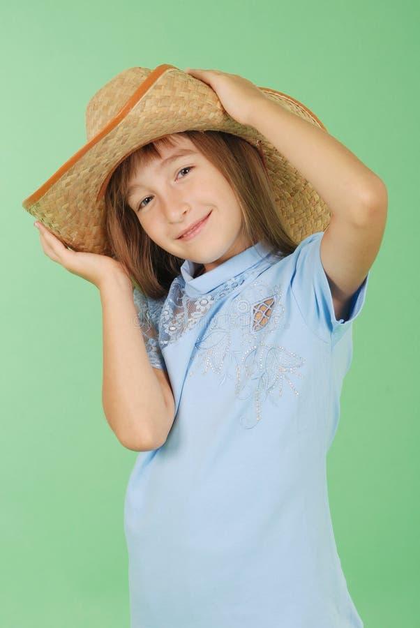 Mädchen, das in der Hand einen Strohhut hält lizenzfreie stockbilder