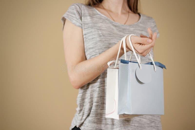 Mädchen, das in der Hand geschenk-Taschenspott des freien Raumes zwei Papieroben hält Leerer pac stockbilder