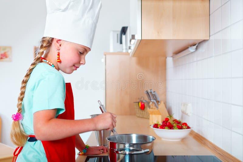 Mädchen, das in der modernen Küche kocht lizenzfreie stockfotos