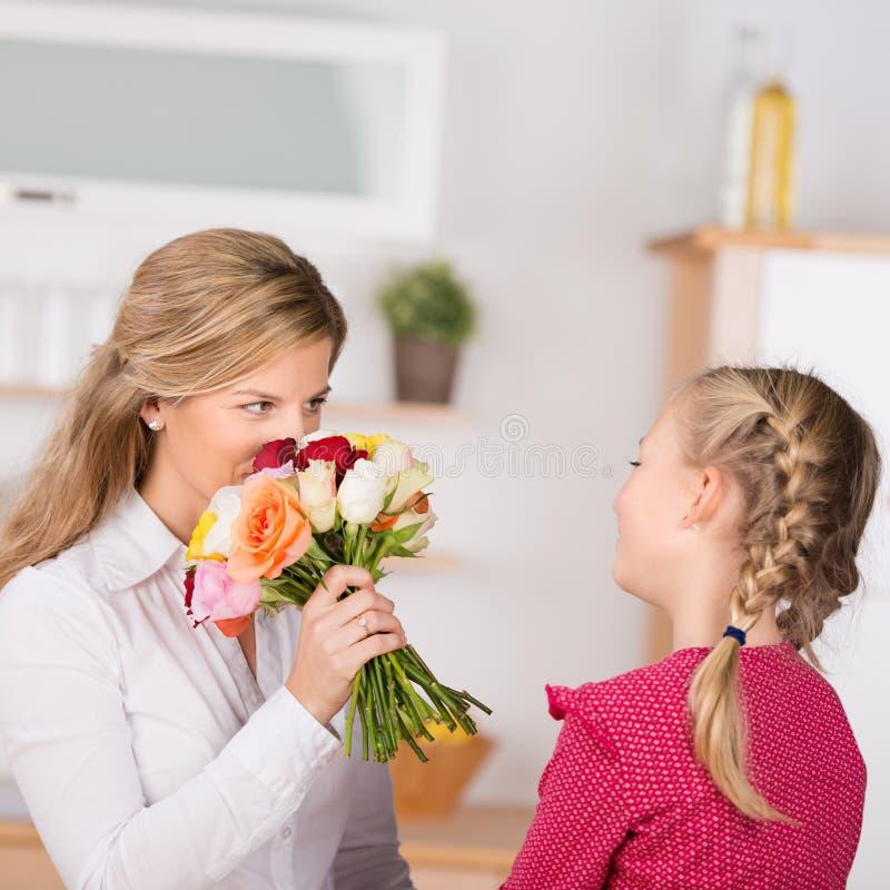 Mädchen, das der Mutter Blumen gibt stockfotos