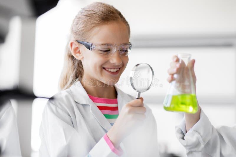 Mädchen, das in der Schule Labor des Reagenzglases studiert lizenzfreies stockbild