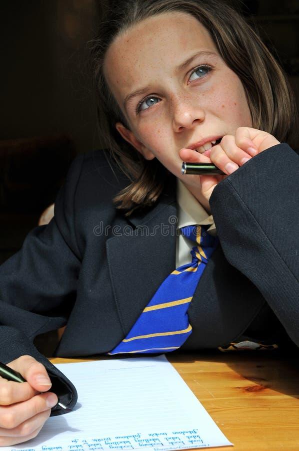 Mädchen, das an der Schule sich konzentriert stockbild