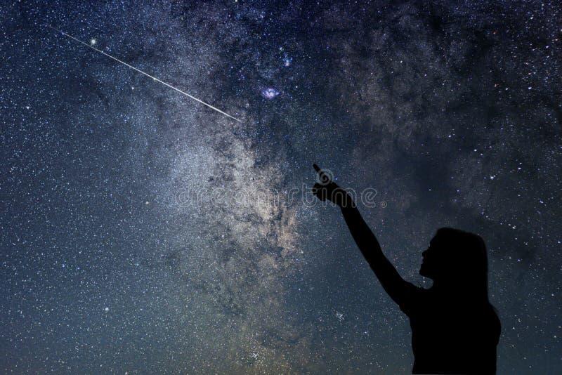 Mädchen, das die Sterne betrachtet Mädchen, das eine Sternschnuppe zeigt lizenzfreie stockbilder