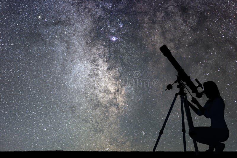 Mädchen, das die Sterne mit Teleskop betrachtet Milchstraßegalaxie lizenzfreie stockfotografie