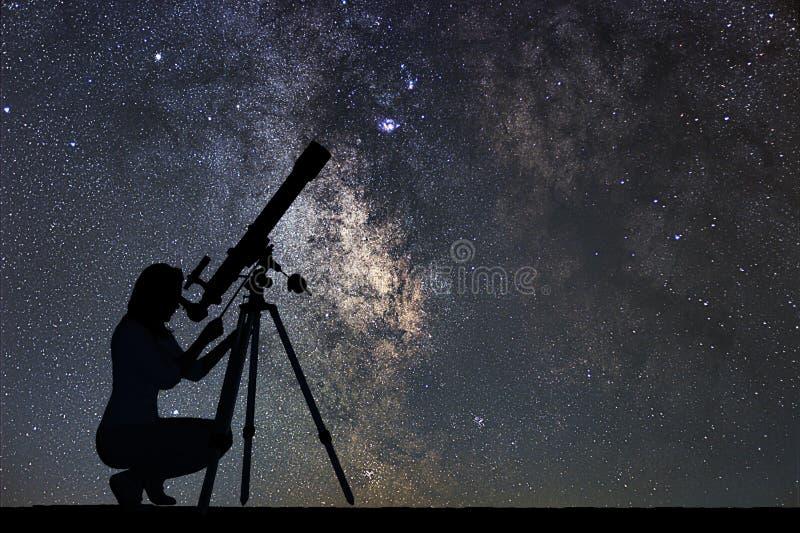 Mädchen, das die Sterne mit Teleskop betrachtet Milchstraßegalaxie lizenzfreie stockbilder
