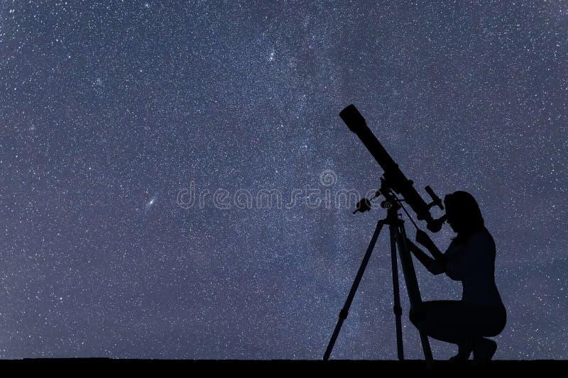 Mädchen, das die Sterne mit Teleskop betrachtet Sternenklarer nächtlicher Himmel stockbild