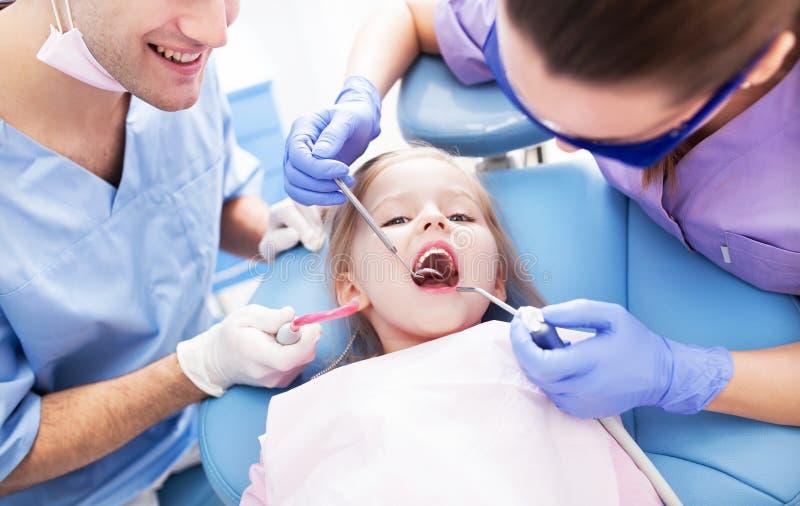 Mädchen, das die Zähne überprüft an den Zahnärzten hat stockfotografie