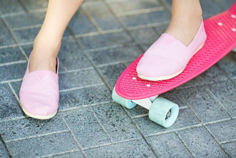 Mädchen, das draußen auf einem rosa Skateboard steht stockfotos
