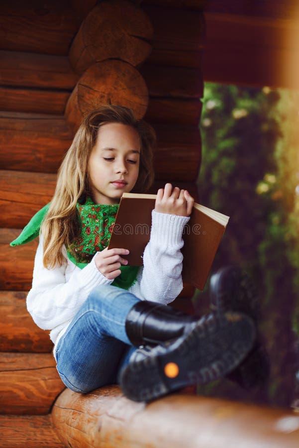Mädchen, das draußen ein Buch liest stockfotografie