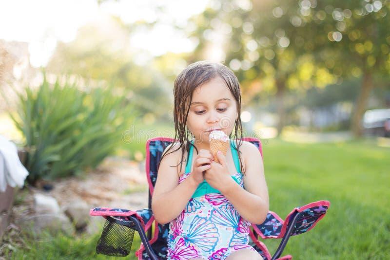 Mädchen, das draußen Eiscreme isst lizenzfreie stockbilder