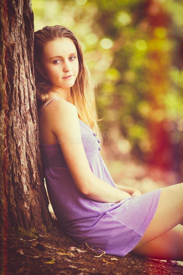 Mädchen, das durch Baum sitzt stockbild