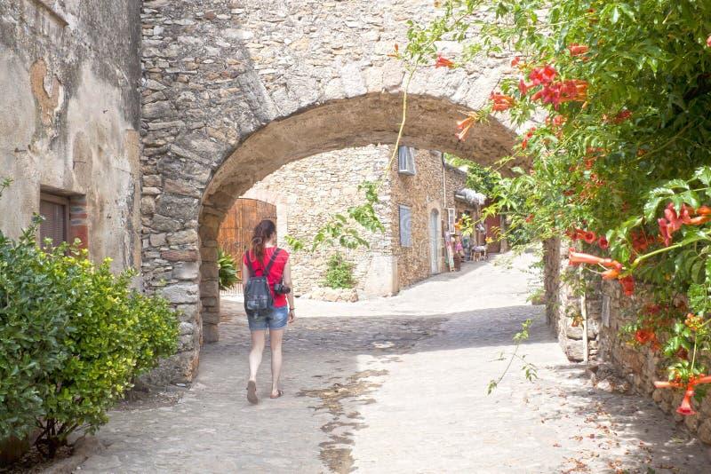 Mädchen, das durch einen Bogen gemacht vom Stein in Peratallada überschreitet lizenzfreies stockbild