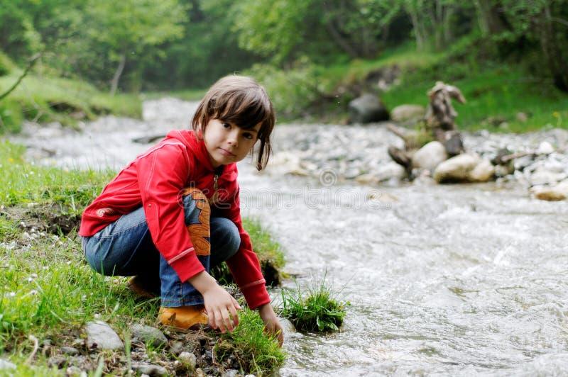 Mädchen, das durch Fluss spielt lizenzfreies stockbild