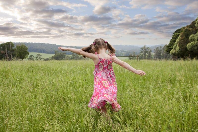 Mädchen, das durch langes Gras läuft lizenzfreie stockbilder