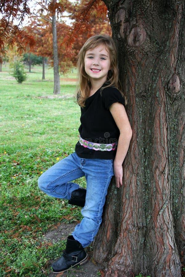 Mädchen, das durch Tree aufwirft lizenzfreies stockfoto