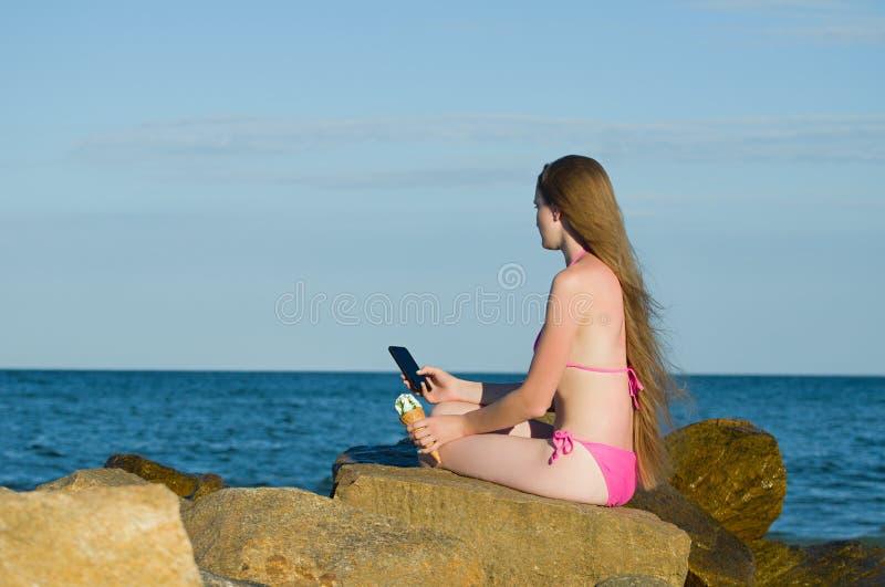 Mädchen, das durchdacht das Telefon, in einem Badeanzug auf dem Strand untersucht stockfotos