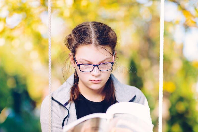 Mädchen, das ein Buch beim Sitzen auf einem Gartenschwingen - fokussierter Gi liest stockfotos